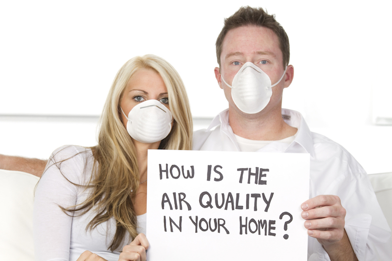 "Couple holding a sign asking ""how is the air quality in your home""?"